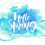 你好春天书法横幅 在蓝色水彩纹理的白色文本 免版税库存照片