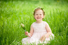Αστείο κοριτσάκι στο στεφάνι του χαμόγελου λουλουδιών Στοκ Φωτογραφία