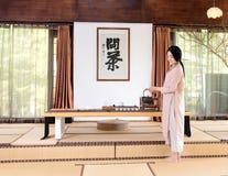 有茶壶中国茶道的一名妇女 免版税图库摄影