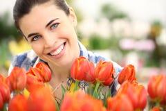 春天,妇女在有花郁金香的庭院里 免版税库存图片