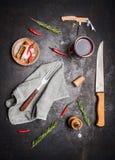 与烹调工具、杯红葡萄酒,草本和香料在黑暗的土气背景的厨房的平的位置 免版税库存照片