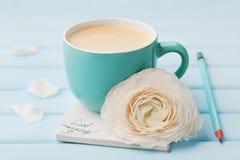 有春天花的咖啡杯和在蓝色土气背景,早餐的笔记早晨好 免版税库存照片