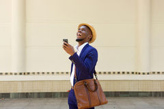 走与手机和袋子的非洲商人 免版税库存照片