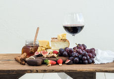 杯红葡萄酒、乳酪板、葡萄、无花果、草莓、蜂蜜和面包条在土气木桌上,白色 库存图片