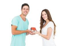Ευτυχές ζεύγος που κρατά το μικροσκοπικό σπίτι Στοκ Εικόνα