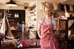 礼品店女性店主画象与数字式片剂的 库存图片