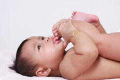 吮她的脚趾的逗人喜爱的亚裔女婴 免版税库存照片