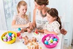 与上色复活节彩蛋的母亲和孩子的家庭 免版税图库摄影