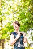 有心脏的小女孩 亚洲妇女微笑愉快在晴朗的夏天或春日外面在开花的树庭院里 相当 免版税库存图片