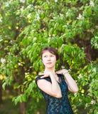 有心脏的小女孩 亚洲妇女微笑愉快在晴朗的夏天或春日外面在开花的树庭院里 相当 免版税库存照片