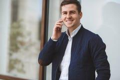年轻商人谈话在手机户外 免版税库存图片