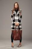 有一个皮革棕色时尚袋子的美丽的妇女 免版税库存图片