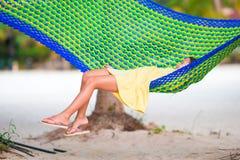 在放松在吊床的热带假期的可爱的小女孩 库存图片