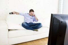 看电视的年轻愉快的人在家坐看起来客厅的沙发放松享用电视 免版税库存照片