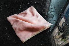 清洁在湿黑花岗岩柜台酒吧的纤维布料 免版税库存照片