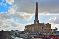 巨大的工厂烟囱和起重机在行动在跟特港口  免版税库存图片