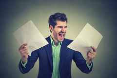 Сердитый кричащий бизнесмен с обработкой документов бумаг документов Стоковые Фото