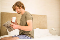 读新闻和喝咖啡的英俊的人 库存照片
