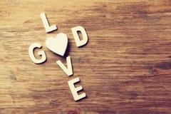 Η εκλεκτική φωτογραφία εστίασης της αγάπης λέξεων είναι Θεός που γίνεται με τις ξύλινες επιστολές φραγμών στο ξύλινο υπόβαθρο δια Στοκ Φωτογραφία