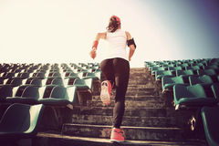 跑在台阶的运动员 妇女健身跑步的锻炼健康概念 图库摄影