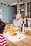 坐在餐桌上的微笑的老婆婆和孙女画象  库存照片