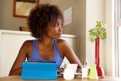 使用数字式片剂的可爱的非洲妇女 免版税库存照片
