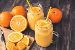 在玻璃瓶子的橙色果子圆滑的人 免版税库存照片