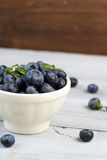 陶瓷碗用在木背景的新鲜的蓝莓 库存图片