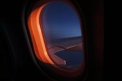 航空公司在翼期间飞行的窗口视图在黄昏的 免版税库存照片
