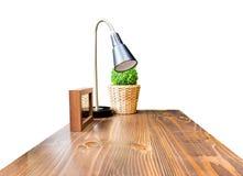 与灯、画框和绿色灌木的木台式在柳条 免版税库存图片