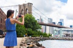 Туристское принимая изображение перемещения с телефоном Бруклинского моста, Нью-Йорка Стоковые Фото