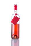 Το ανοιγμένο μπουκάλι αυξήθηκε κρασί στο άσπρο υπόβαθρο Στοκ Εικόνες