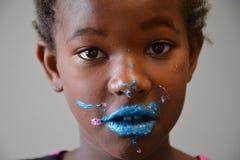 有明亮的蓝色结霜的非裔美国人的女孩在面孔 库存照片