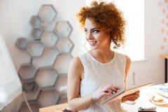 Εύθυμη νέα επιχειρησιακή γυναίκα που χρησιμοποιεί την ταμπλέτα στην αρχή Στοκ Φωτογραφία