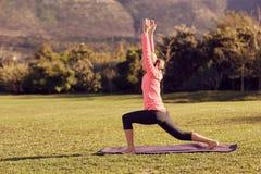 户外适合资深妇女的边在瑜伽姿势 免版税库存照片