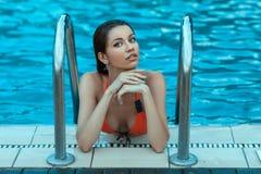 在游泳的湿妇女在水池以后 库存图片