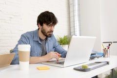 工作在计算机家庭办公室的年轻西班牙行家商人 免版税库存照片