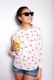 摆在白色背景的演播室的美丽的女孩 饮用的汁液桔子 免版税库存图片
