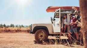 在旅行读书的年轻夫妇为方向映射 库存图片