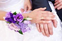 有定婚戒指的手在新娘花束 库存照片
