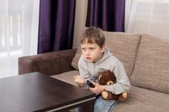 紧张的孩子坐沙发和观看的电视 免版税库存图片