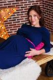 时尚孕妇在有装饰的演播室 库存图片