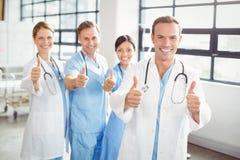 Ιατρική ομάδα που βάζει τους αντίχειρές τους επάνω και που χαμογελά Στοκ φωτογραφία με δικαίωμα ελεύθερης χρήσης