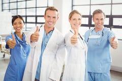 Ιατρική ομάδα που βάζει τους αντίχειρές τους επάνω και που χαμογελά Στοκ Εικόνες