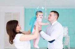 父亲、母亲和他们的小女儿在屋子里使用 免版税库存图片