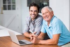微笑的父亲和儿子画象有膝上型计算机的 库存图片