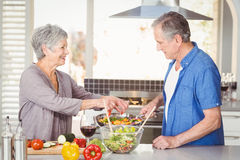 准备食物的愉快的资深夫妇侧视图  免版税图库摄影
