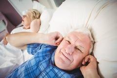 人从打鼾的妻子的覆盖物耳朵画象  免版税库存图片