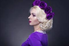白肤金发的白种人妇女佩带的紫罗兰色用花装饰的生动的冠画象  免版税库存照片