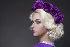 白肤金发的白种人妇女佩带的紫罗兰色用花装饰的冠画象  免版税库存照片